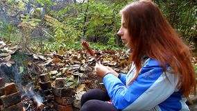 Young girl fry sausage on a fire outdoors and eat stock video