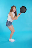 Young girl with a frying pan Royalty Free Stock Photos