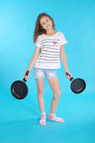 Young girl with a frying pan Stock Photos
