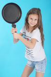 Young girl with a frying pan Royalty Free Stock Photography