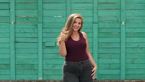 A young girl with a full figure walks in the Park. Portrait of a young girl overweight in the city Park on the background of a green wooden fence. Slow motion stock video