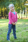 Young girl full length standing on green grass in park Stock Photo