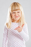 Young girl with funny grin. Studio portrait of young girl showing funny grin and hand gesture royalty free stock image