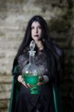 Young girl with fur cape and flask with potion. Looking like Halloween suit. Stock Image
