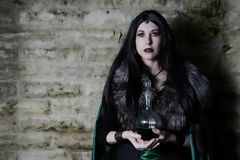 Young girl with fur cape and flask with potion. Looking like Halloween suit. Royalty Free Stock Image