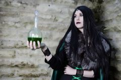 Young girl with fur cape and flask with potion. Looking like Halloween suit. Stock Photography