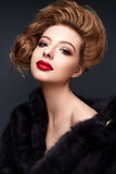 Young girl in a fur coat and bright makeup. Beautiful model with red lips and hairstyle. Photo is taken in a studio. Beauty of the face Royalty Free Stock Images