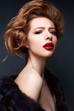 Young girl in a fur coat and bright makeup. Beautiful model with red lips and hairstyle. Photo is taken in a studio. Beauty of the face Royalty Free Stock Photos