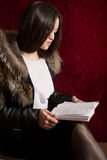 Young girl in a fur coat sitting back and reading the manuscript Royalty Free Stock Photos
