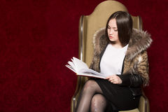 Young girl in a fur coat sitting chair and reading a book Royalty Free Stock Image