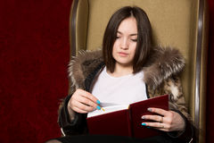 Young girl in a fur coat sitting chair and reading a book. Asian woman studying diary Royalty Free Stock Photos
