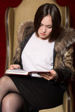 Young girl in a fur coat sitting chair and reading a book Stock Image