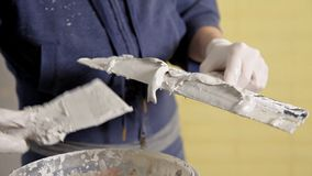 Young girl gaining putty paste from a bucket on a spatula. Home repair.  stock video footage