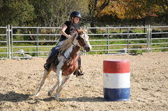 Young girl galloping around a barrel during a barrel race Royalty Free Stock Photo