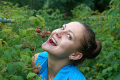 Young girl in garden with raspberries in the mouth Royalty Free Stock Image