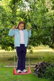 Young girl on the garden swing Royalty Free Stock Photography