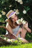 Young girl gardening among white roses Stock Photo