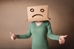 Young girl gesturing with brown cardboard box on her head with s. Young girl standing and gesturing with brown cardboard box on her head with sad face Stock Images