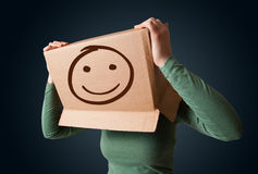 Young girl gesturing with a cardboard box on her head with smile Stock Image