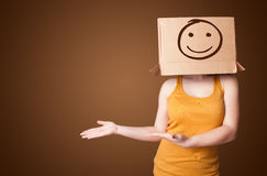 Young girl gesturing with a cardboard box on her head with smile. Young girl standing and gesturing with a cardboard box on her head with smiley face Stock Photo