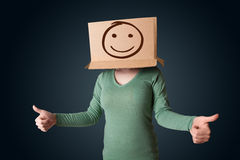 Young girl gesturing with a cardboard box on her head with smile. Young girl standing and gesturing with a cardboard box on her head with smiley face Royalty Free Stock Image