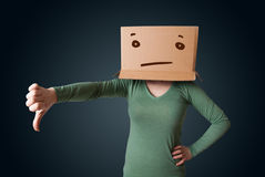 Young girl gesturing with a cardboard box on her head with strai Stock Image