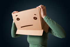 Young girl gesturing with a cardboard box on her head with strai Royalty Free Stock Photography