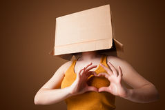 Young girl gesturing with a cardboard box on his head Stock Photography