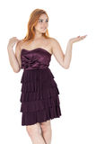 Young girl gesturing with hands for presentation. Redheaded girl. Friendly girl stands with palm up. She has something. Redheaded teenager wearing dark purple Stock Images