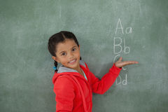 Young girl gesturing over chalk board. Portrait of young girl gesturing over chalk board Royalty Free Stock Photo