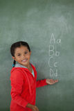 Young girl gesturing over chalk board. Portrait of young girl gesturing over chalk board Stock Image