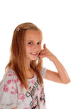 Young girl gesturing a phone call. Stock Photo