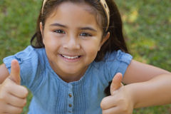 Young girl gesturing thumbs up at park Royalty Free Stock Image