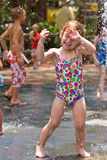 Young girl getting sprayed in the face. A young girl gets sprayed in the face with water while playing on a hot summer afternoon Royalty Free Stock Images