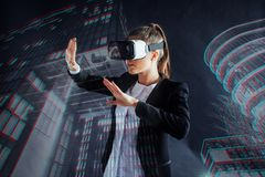 Young girl getting experience VR headset, is using augmented reality eyeglasses, being in a virtual reality. In city at Stock Images