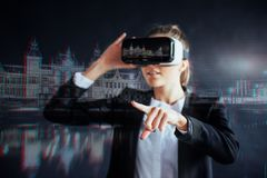 Young girl getting experience VR headset, is using augmented reality eyeglasses, being in a virtual reality. In city at Royalty Free Stock Images