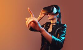 Young girl getting experience VR headset is using augmented reality eyeglasses being in virtual reality. Girl with hands. Up wearing the virtual reality goggles