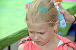 Young girl getting her hair spray painted Royalty Free Stock Photos
