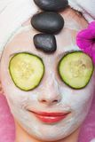 Young girl getting spa treatment with facial mask. A cute young girl getting a luxurious spa treatment including a facial mask, cucumber slices over her eyes and Stock Photo