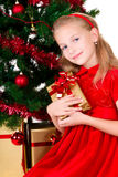 Young girl with gift. Young girl with gift sit near Christmas tree Royalty Free Stock Photos