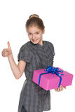 Young girl with a gift box holds her thumb up Stock Photo