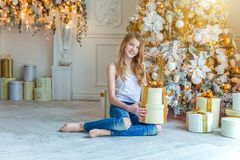 Young girl with gift box near Christmas tree at home royalty free stock images