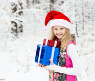 Young girl with gift box and santa hat in winter forest Royalty Free Stock Image