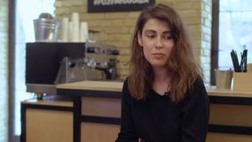 Young girl give interview in cafe. Young woman give an interview. Pretty girl sits in front of the bar in cafe and talk about her life. Prores codec stock video