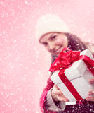 Young girl gives a christmas gift in snow Royalty Free Stock Photo