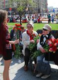 Young girl gives flowers to war veterans Royalty Free Stock Images