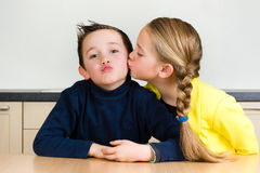 Young girl gives her brother a kiss Stock Photography