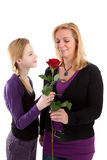 Young girl gives rose to mother Stock Image