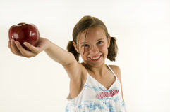 Young girl giving an apple. A young girl holding out an apple isolated on white Stock Photos