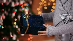 Young girl giving a christmas present - closeup on hands stock footage
